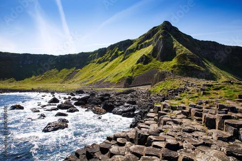 Krajobraz szlaku Giant's Causeway z błękitnym niebem latem w Irlandii Północnej, hrabstwo Antrim. Dziedzictwo UNESCO. Jest to obszar bazaltowych kolumn, będący wynikiem dawnej erupcji szczeliny wulkanicznej