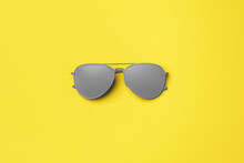 Gray Painted Sunglasses On Yellow Background Top View