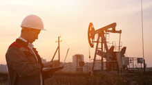 Man In A White Helmet With A Laptop On The Background Of An Oil Rocking At Sunset.