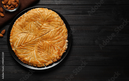 Obraz Traditional galette des rois and almonds on black wooden table, flat lay. Space for text - fototapety do salonu
