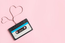 Top View Of Music Cassette And Hearts Made With Tape On Pink Background, Space For Text. Listening Love Song