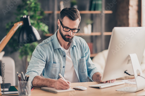 Photo portrait of guy writing in notebook working on pc at table in modern industrial office indoors