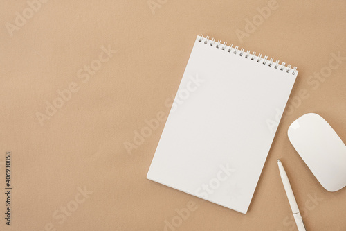 Flatlay of blank sheet spiral notebook, mouse, pen on pastel beige table. Flat lay, top view. Copy space mockup template background.
