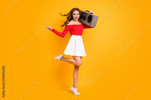 Obraz Full length body size photo girl keeping boom-box on shoulder enjoying music party isolated on bright yellow color background - fototapety do salonu
