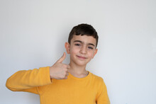 Positive Child Shows A Hand Gesture Of An Agreement, Like, Approval Neutral Background. Boy Showing Thumbs Up And Looking At Camera, Isolated. Turkish Boy.