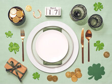 Beautiful Festive Table Setting For St.Patrick's Day With Cutlery And Lucky Symbols. Top View Of Saint Patrick's Day Holiday Table With Green Linen Tablecloth. Copy Spase In Center. Flat Lay.