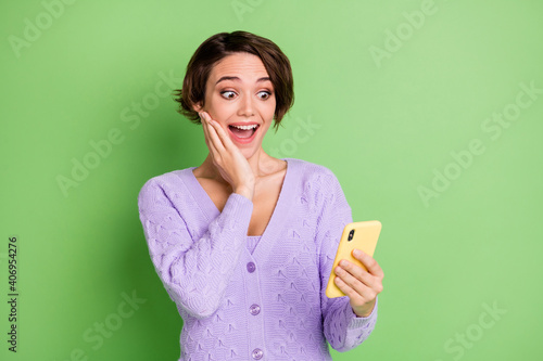 Fotografering Photo of impressed attractive girl hand on cheek open mouth staring phone isolat