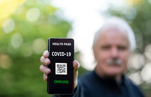 Senior Man Showing An Vaccination Certificate On A Mobile Phone, Which Indicates A Vaccination Against Covid-19.