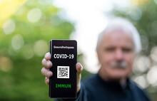 Älterer Herr Zeigt Digitalen Impfpass Auf Dem Smartphone, Auf Dem Eine COVID-19 Impfung Nachgewiesen Wird.