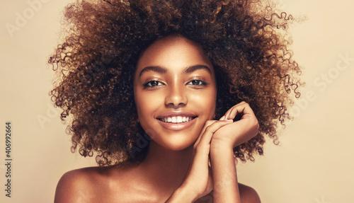 Beauty portrait of african american woman with clean healthy skin on beige background. Smiling beautiful afro girl.Curly black hair. Black teen girl - fototapety na wymiar