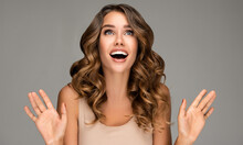 Beautiful Shocked And Surprised Woman Screaming And  Looking Up Presenting  Your Product . Curly Hair Girl Amazed . Expressive Facial Expressions . Beauty And Cosmetology