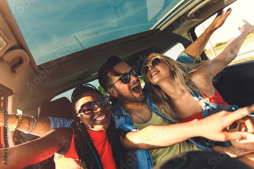 Obraz Three best friends enjoying traveling in the car, sitting in rear seat and having lots of fun on a road trip. - fototapety do salonu