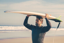Male Surfer In Wetsuit Walking On Beach And Carrying Surfboard Overhead. Medium Shot. Surfing And Active Lifestyle Concept