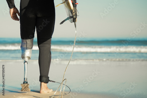 Obraz Unrecognizable disabled surfer going to water and carrying longboard. Cropped strong man wearing sportive swimsuit and holding surfboard. Physical disability, surfing and extreme sport concept - fototapety do salonu