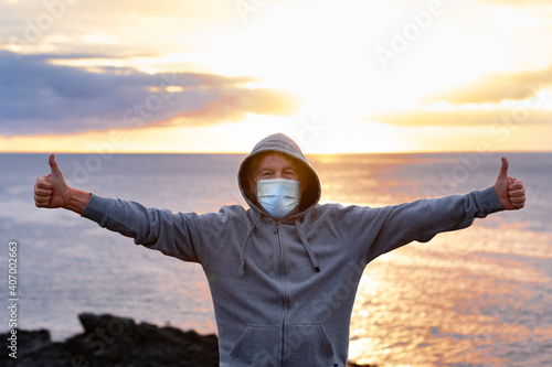 Obraz Front view of senior man with hood on head standing on top of cliff with ocean behind him. One people enjoying a winter day at sea with raised arms, wearing surgical mask due to coronavirus - fototapety do salonu