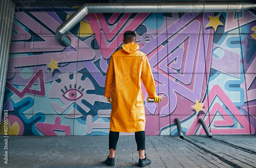 Back view of graffiti painter looking to the wall with his paintings