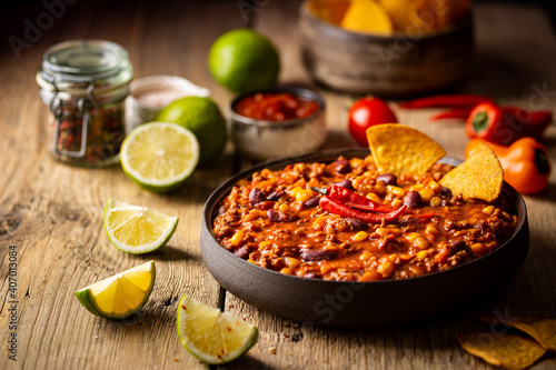 Canvas Mexican hot chili con carne in a bowl with tortilla chips on wooden background