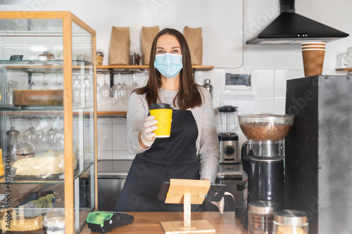 A female barista wearing protective mask and gloves giving a takeaway cup of coffee, safety measures during viral diseases, coronavirus pandemic. Small business works during lockdown © Вадим Пастух