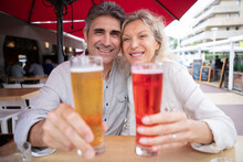 Senior Couple Enjoying Drinks On Restaurant Terrace