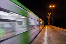 Night Outdoor Scenery Of Platform Railway Station And Regional Train With Blur Motion.