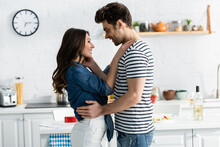 Side View Of Joyful Couple Looking At Each Other And Hugging In Kitchen