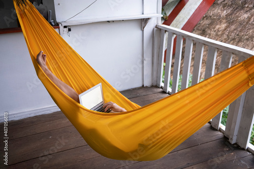 Fotografie, Obraz Digital nomad woman who works on a hammock hanging in a cabin in the jungle