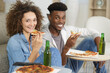 portrait of a young couple eating pizza at home