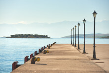 Parallel Row Of Lighthouses And A Pier With A View Of The Lake And Mountains In The Background, Greece