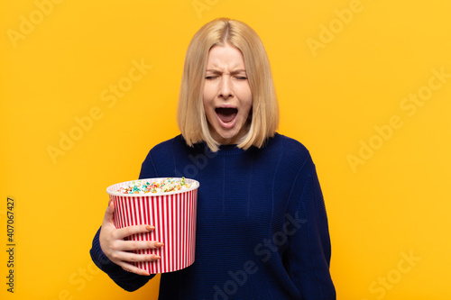 Vászonkép blonde woman shouting aggressively, looking very angry, frustrated, outraged or