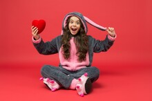 Happy Little Girl Hold Red Heart Love Symbol Wearing Bunny Pajamas For Valentines Day, 14 February