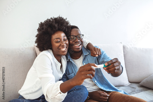 Fotografie, Obraz Joyful couple finding out results of a pregnancy test at home