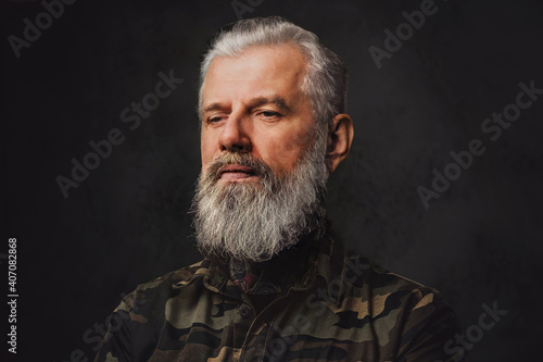 Fototapeta Brutal martial grandfather dressed in military clothing poses in dark background