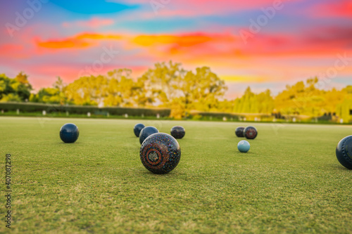 Obraz Lawn bowls balls in a field after the game with a colourful sunset - fototapety do salonu