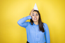 Young Caucasian Woman Wearing A Birthday Hat Over Isolated Yellow Background Putting One Hand On Her Head Smiling Like She Had Forgotten Something