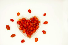 Tomatoes Surrounding Heart-shaped Bowl With Content Of Red Cherry Tomatoes In Aerial View