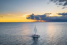 Aerial View Of Catamaran Boat Full Of People Sailing Under An Orange Sunset, La Altagracia, Dominican Republic