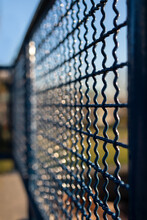 Abstract Railing Texture With Bokeh And Lights Dapples. Defocused Perspective View Of Blue Metal Park Fence With Bright Blue And Green Background. Wave Pattern On Fence.