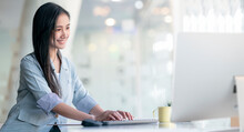 Young Beautiful Asian Woman Working On Computer With Happiness While Sitting At Her Office Desk In Modern Office.