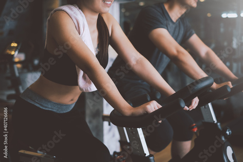 Obraz Asian man and woman they are enjoys cycling in the gym because it keeps his legs strong and healthy. - fototapety do salonu