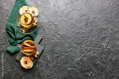 Tasty drink with spices and apple slices in cups on dark background © Pixel-Shot