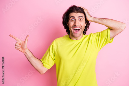 Photo of impressed person arm on head open mouth unbelievable direct finger empty space isolated on pink color background