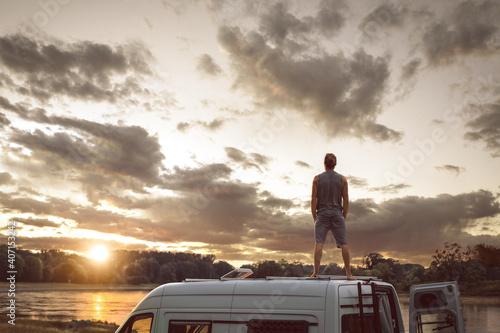Obraz na płótnie Man enjoying the sunset on the roof of his camper van
