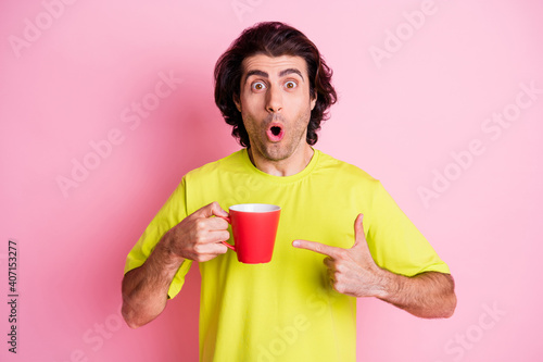 Photo of impressed amazed young charming man point finger tea cup wear yellow t-shirt isolated on shine pink color background