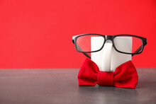Funny Composition With Bow Tie, Glasses And Cup On Grey Table Against Red Background. Space For Text