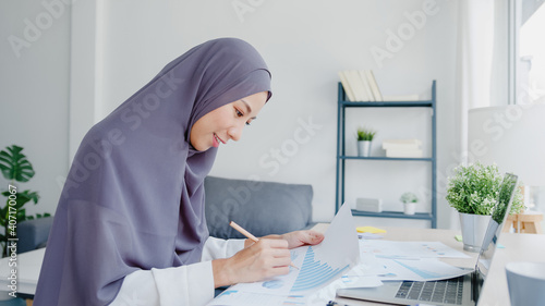 Beautiful Asia muslim lady in headscarf casual wear using laptop in living room at house. Remotely working from home, new normal lifestyle, social distancing, quarantine for corona virus prevention.