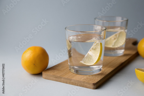 Fotomural Water with lemon in two glasses on a wooden stand on a light blue background, sl