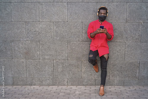 Happy african young man listening music with headphones outdoors while wearing safety mask - Focus on face