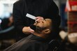 Black man in the barbershop. Cute black man makes a haircut in the African salon. Hair style. Haircut for adults.