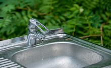 Defective Faucet. Cause Wastage Of Water. Water Tap Outdoor Green Park Background. Please, Save Water