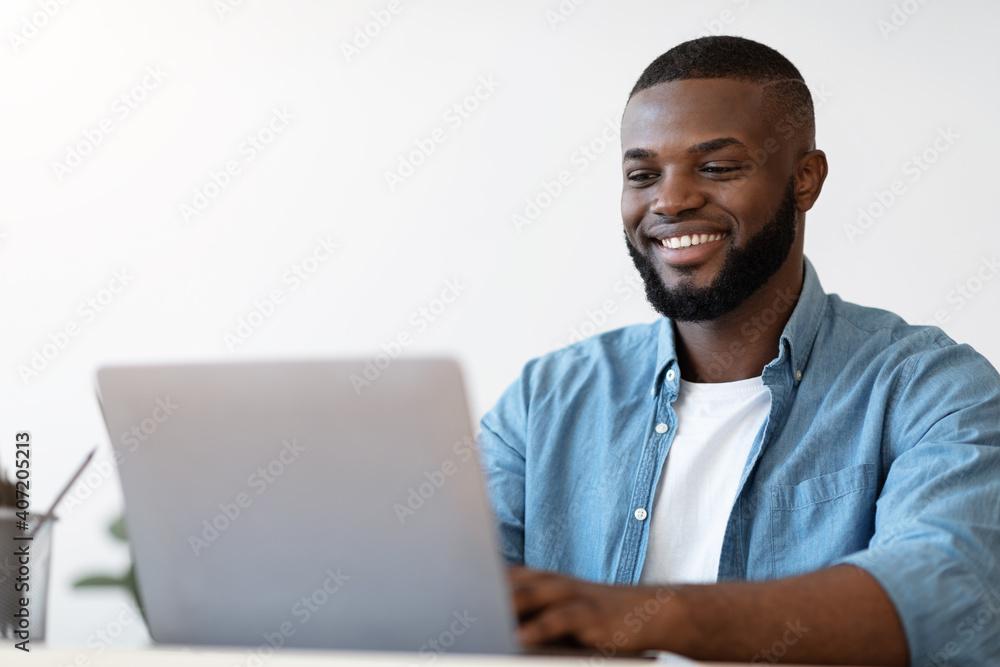 Fototapeta Handsome Black Male Office Employee Working On Laptop Computer, Closeup Shot